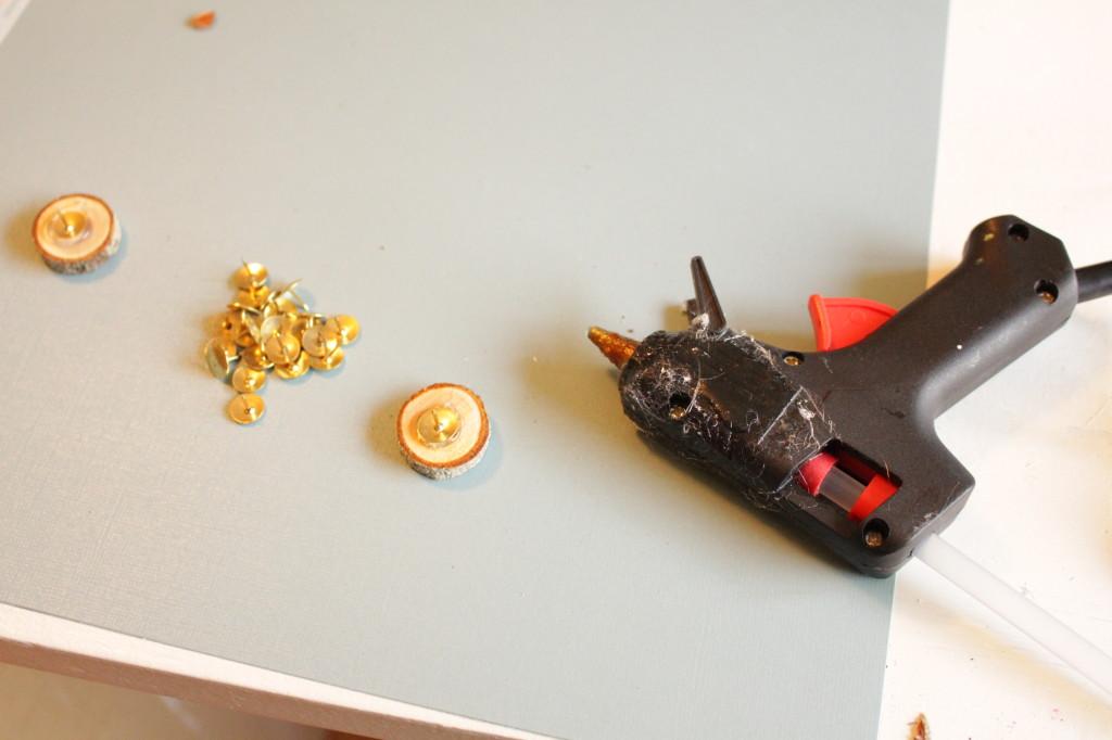 Hot glue gun and wooden discs.